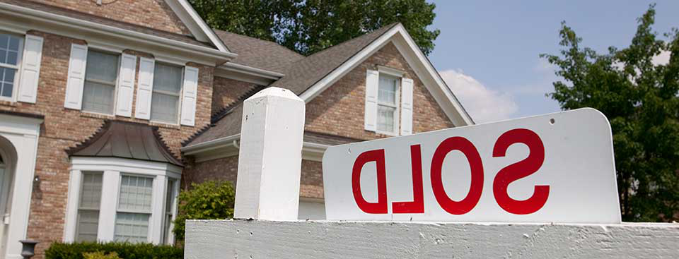 Sold house sign in suburban setting. Focus on sign.