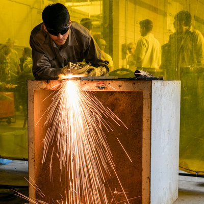 ACC student welding with sparks flying.